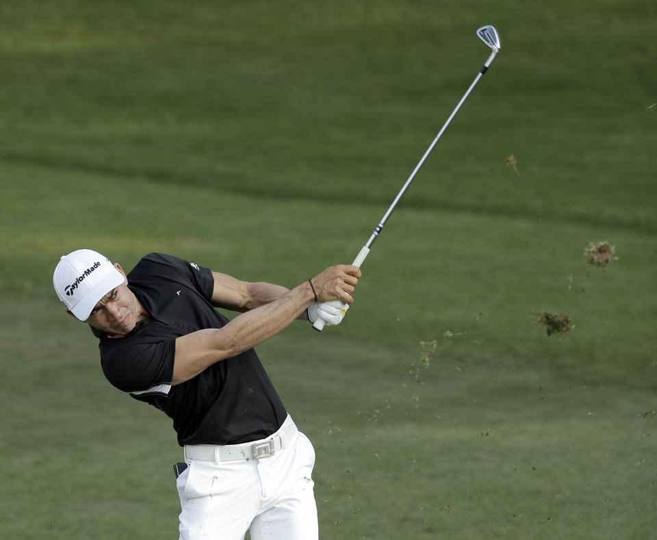 Photo - Camilo Villegas, of Colombia, hits his approach shot on the ninth hole during the first round of the Wyndham Championship golf tournament in Greensboro, N.C., Thursday, Aug. 14, 2014. (AP Photo/Chuck Burton)