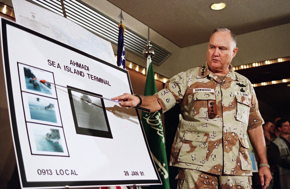 Photo - FILE - In this Jan. 27, 1991 file photo, U.S. Army Gen. Norman Schwarzkopf points to row of photos of Kuwait's Ahmadi Sea Island Terminal on fire after a U.S. attack on the facility. Schwarzkopf died Thursday, Dec. 27, 2012 in Tampa, Fla. He was 78. (AP Photo/Laurent Rebours, File)