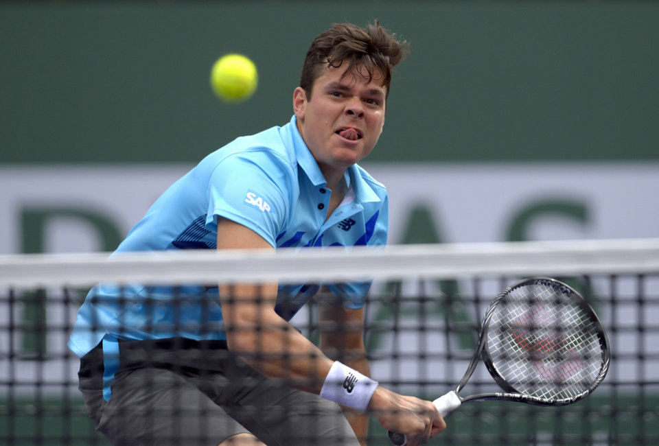 Photo - Milos Raonic, of Canada, hits to Alexandr Dolgopolov, of Ukraine, during a quarterfinal at the BNP Paribas Open tennis tournament, Thursday, March 13, 2014, in Indian Wells, Calif. (AP Photo/Mark J. Terrill)