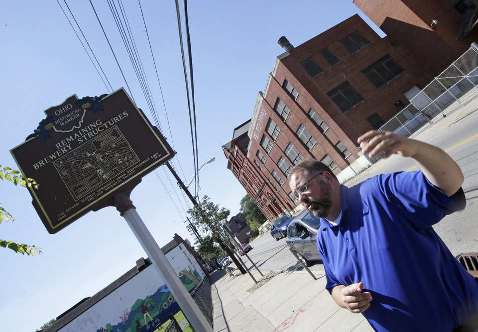Photo - Steve Hampton, a local architect and the part-time executive director of the nonprofit Brewery District Community Urban Development Corp., stands near a sign showing the history of the brewery district, Wednesday, June 19, 2013, in Cincinnati.  The Clyffside-Sohn brewery in the background was one of 18 large breweries that operated in the Over-the-Rhine neighborhood of the city in the late 19th century. (AP Photo/Al Behrman)