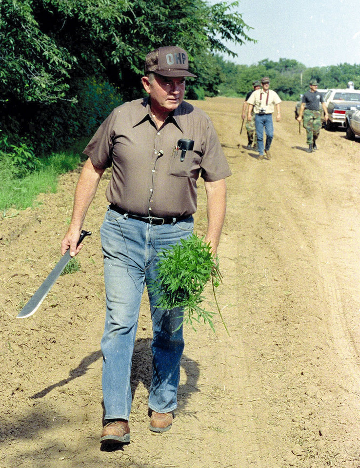 Oklahoma Gov. Henry Bellmon carries several marijuana plants that he cut down using the machete he is holding Thursday Aug. 24, 1989 near Hinton, Oklahoma. Bellmon was on hand to inspect the destruction of more than 180,000 plants by the Oklahoma Highway Patrol and sheriff\'s deputies. (AP Photo/str-Scott Andersen)