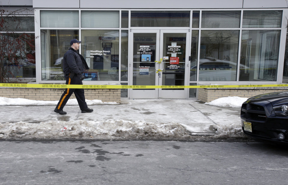 Photo - Police officers stand guard outside the closed post office in Wood-Ridge, N.J., Friday, Jan. 31, 2014. The FBI says a powder mailed to several locations in New York and New Jersey, including at least five hotels near the site of Sunday's Super Bowl, appears not to be dangerous. (AP Photo/Mel Evans)