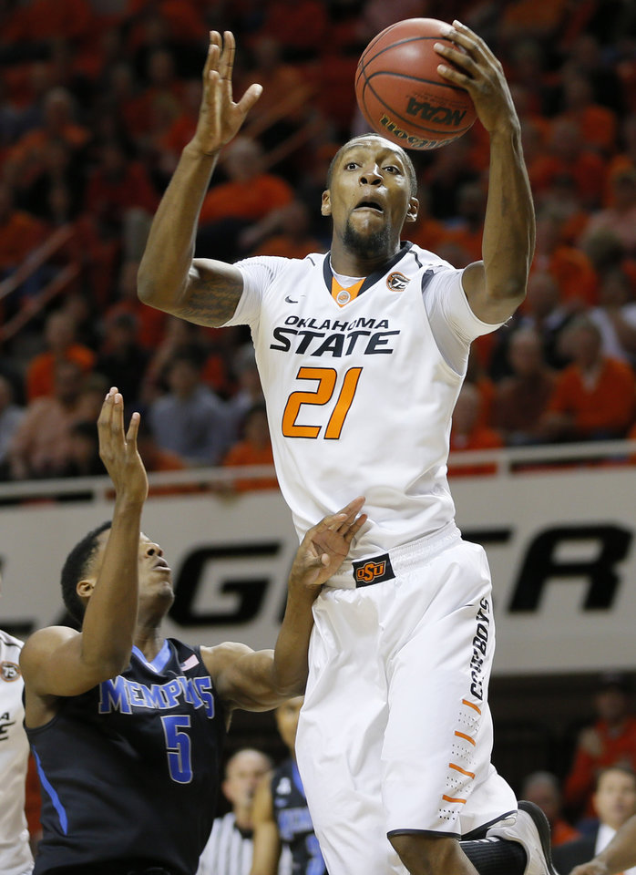 Photo - Oklahoma State's Kamari Murphy (21) grabs a rebound over Memphis' Nick King (5) during an NCAA college basketball game between Oklahoma State and Memphis at Gallagher-Iba Arena in Stillwater, Okla., Tuesday, Nov. 19, 2013. Photo by Bryan Terry, The Oklahoman