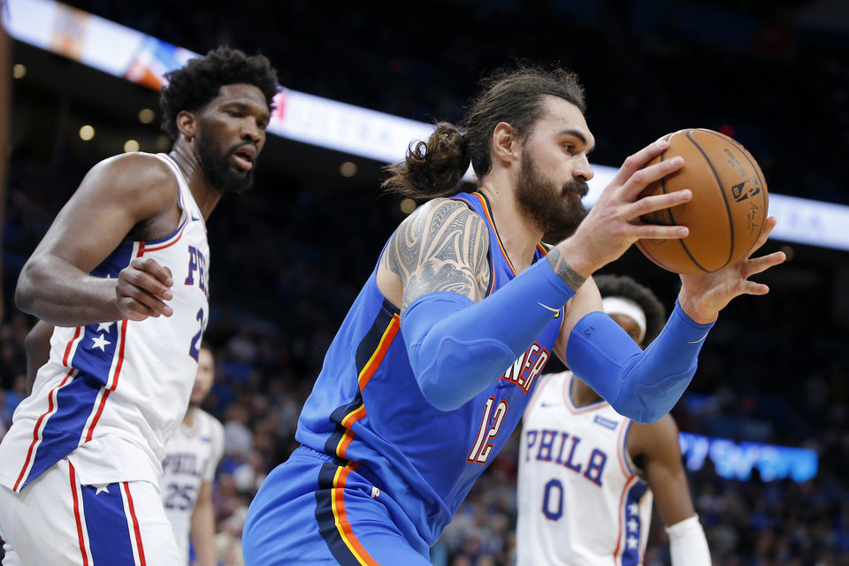 Photo - Oklahoma City's Steven Adams (12) gains control of the ball in front of Philadelphia's Joel Embiid (21) during an NBA basketball game between the Oklahoma City Thunder and the Philadelphia 76ers at Chesapeake Arena in Oklahoma City, Friday, Nov. 15, 2019. Oklahoma City won 127-119. [Bryan Terry/The Oklahoman]
