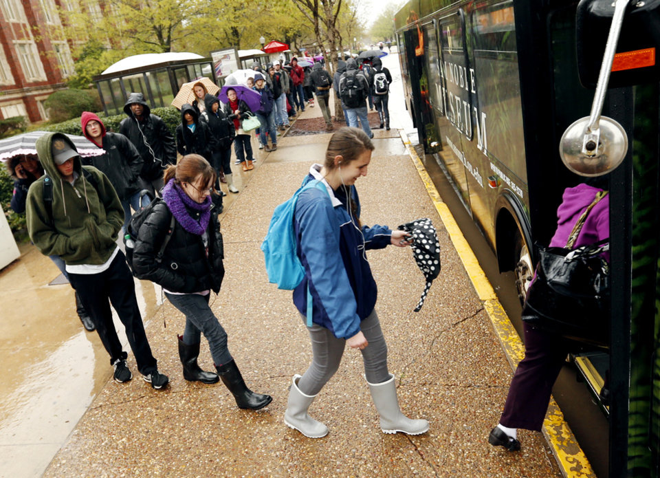 Photo - Students wait in the rain for a bus at the University of Oklahoma on Wednesday, April 10, 2013 in Norman, Okla.,  Photo by Steve Sisney, The Oklahoman