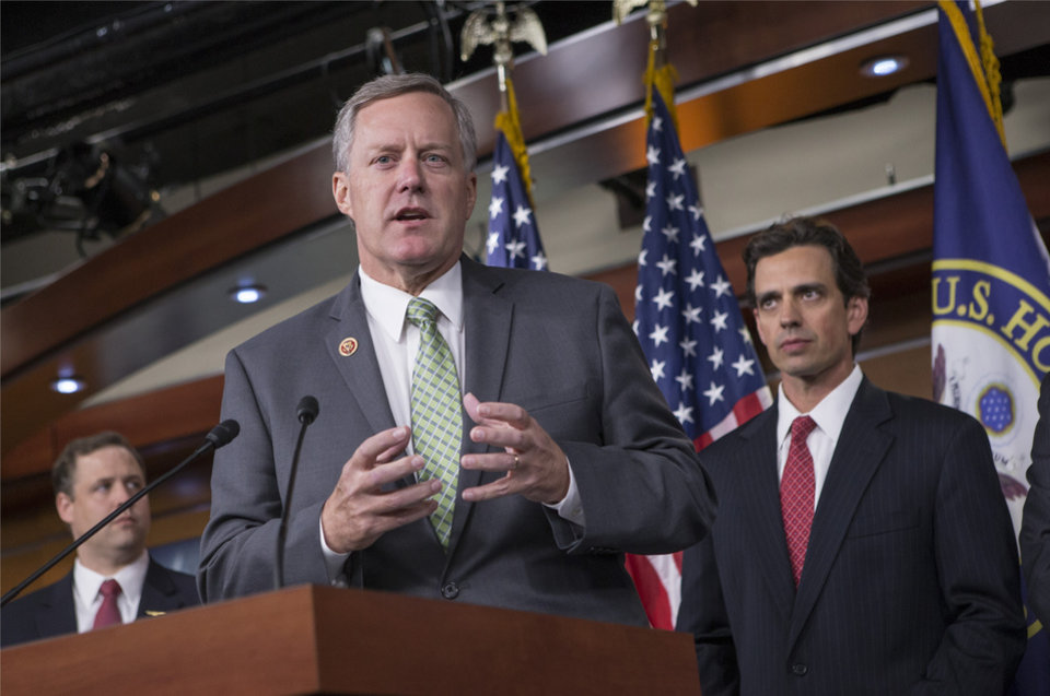 Photo - Rep. Mark Meadows, R-N.C, center, Rep. Tom Graves, R-Ga., right, and other conservative Republicans discuss their goal of obstructing the Affordable Care Act, popularly known as Obamacare, as part of a strategy to pass legislation to fund the government, on Capitol Hill in Washington, Thursday, Sept. 19, 2013. (AP Photo/J. Scott Applewhite)