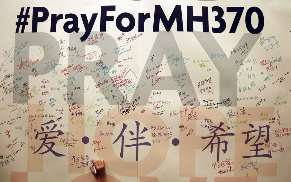 Photo - A man writes messages for passengers aboard the missing Malaysia Airlines Flight MH370 before a mass prayer for them, in Kuala Lumpur, Malaysia, Sunday, April 6, 2014. The head of the multinational search for the missing Malaysia airlines jet said that electronic pulses reportedly picked up by a Chinese ship are an encouraging sign but stresses they are not yet verified. (AP Photo/Lai Seng Sin)