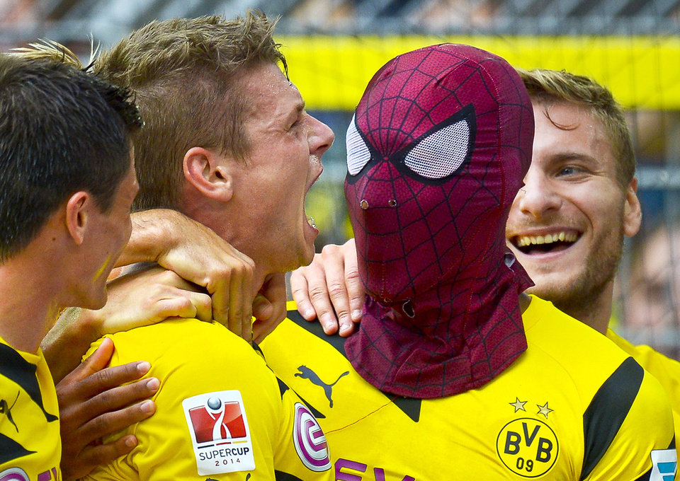 Photo - Dortmund's Pierre-Emerick Aubameyang, right, wears a Spiderman mask as he celebrates after scoring his side's second goal  during the German soccer Super Cup match between Borussia Dortmund and Bayern Munich in Dortmund, Germany, Wednesday, Aug. 13, 2014. (AP Photo/Sascha Schuermann)