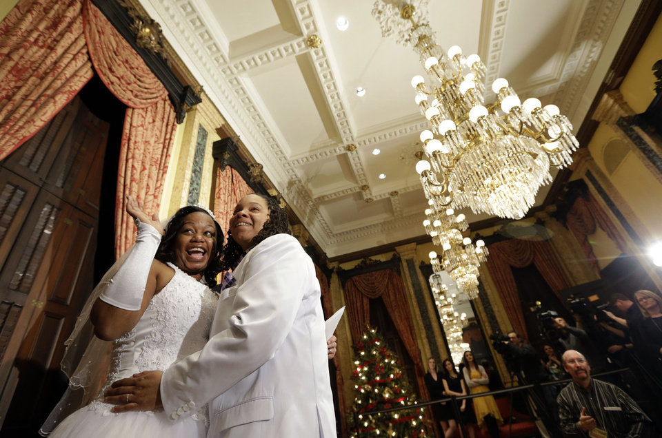Photo - Darcia Anthony, left, and Danielle Williams react after participating in a wedding ceremony at City Hall in Baltimore, Tuesday, Jan. 1, 2013. Same-sex couples in Maryland are now legally permitted to marry under a new law that went into effect after midnight on Tuesday. Maryland is the first state south of the Mason-Dixon Line to approve same-sex marriage. (AP Photo/Patrick Semansky)