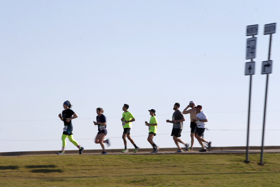 Photo -  Runners make their way west on Britton Road toward Lake Hefner during the Oklahoma City Memorial Marathon on Sunday. [PHOTO BY BRYAN TERRY, THE OKLAHOMAN]