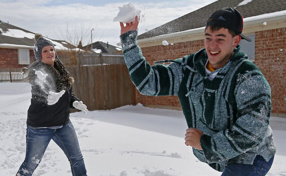 Bailey Parkman, left, throws a snowball at Christian Joy after winter storm left a blanket of snow on the ground outside a  northwest Oklahoma City area neighborhood near 164th and Pennsylvania, Friday, December 6, 2013. Photo by Bryan Terry, The Oklahoman