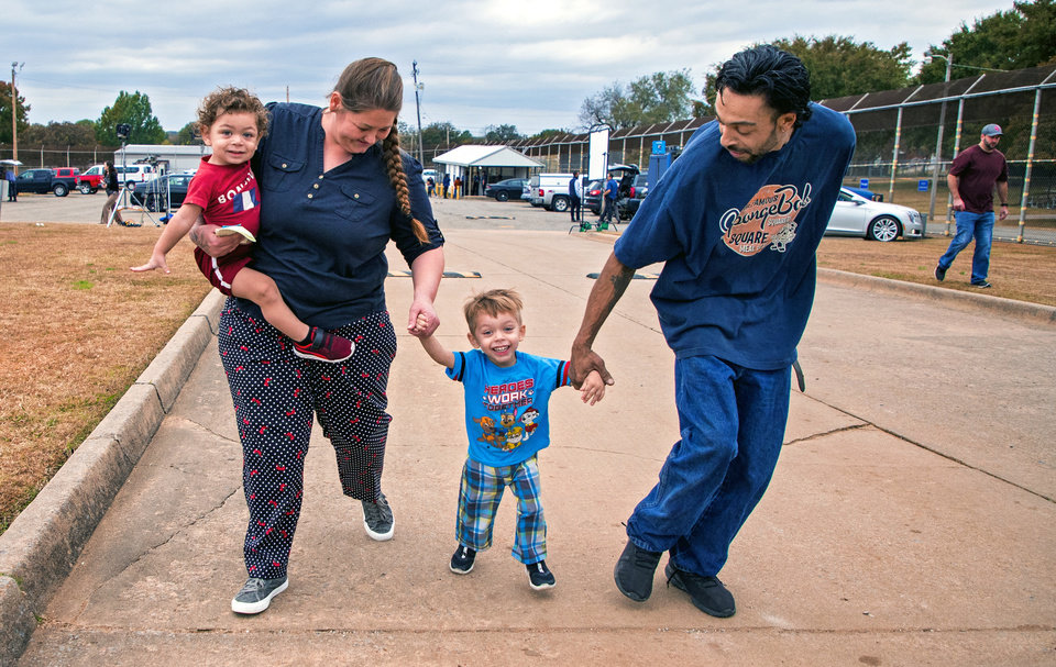 Photo - Donnie Crow, left, carries her son Fayedon Davis, 17 months, while she walks with her son Christopher Davis Jr. and Christopher Davis Sr. after Crow was released from the Dr. Eddie Warrior Correctional Facility on Monday, Nov. 4, 2019 in Taft, Okla. Governor Kevin Stitt greeted an estimated 70 women whose sentences he commuted from the facility. [Chris Landsberger/The Oklahoman]