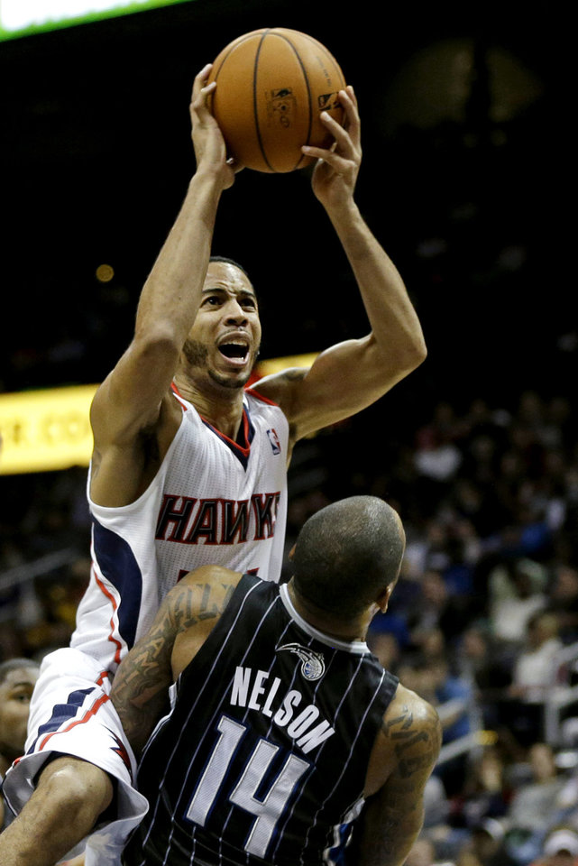 CORRECTS HAWKS PLAYER TO DEVIN HARRIS, NOT LOUIS WILLIAMS - Atlanta Hawks' Devin Harris shoots over Orlando Magic's Jameer Nelson (14) in the second quarter of an NBA basketball game, Monday, Nov. 19, 2012, in Atlanta. (AP Photo/David Goldman)