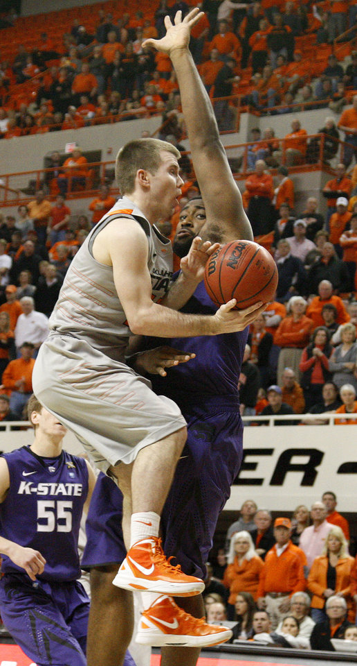Photo - Oklahoma State's Keiton Page (12) is fouled by Kansas State's Thomas Gipson (42) during an NCAA college basketball game between the Oklahoma State University Cowboys (OSU) and the Kansas State University Wildcats (KSU) at Gallagher-Iba Arena in Stillwater, Okla., Saturday, Jan. 21, 2012. Photo by Bryan Terry, The Oklahoman