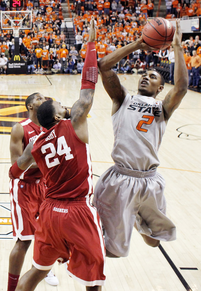 Photo - OSU's Le'Bryan Nash (2) shoots over Romero Osby (24) of OU in the first half during the Bedlam men's college basketball game between the Oklahoma State University Cowboys and the University of Oklahoma Sooners at Gallagher-Iba Arena in Stillwater, Okla., Monday, Jan. 9, 2012. Photo by Nate Billings, The Oklahoman