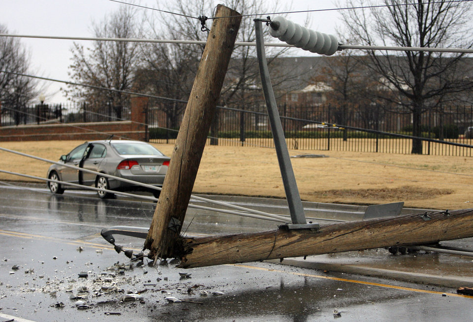 Photo - High line poles blown over on a cars on north Penn just south of 150 in Oklahoma City, Tuesday , February 10, 2009.  By David McDaniel, The Oklahoman.