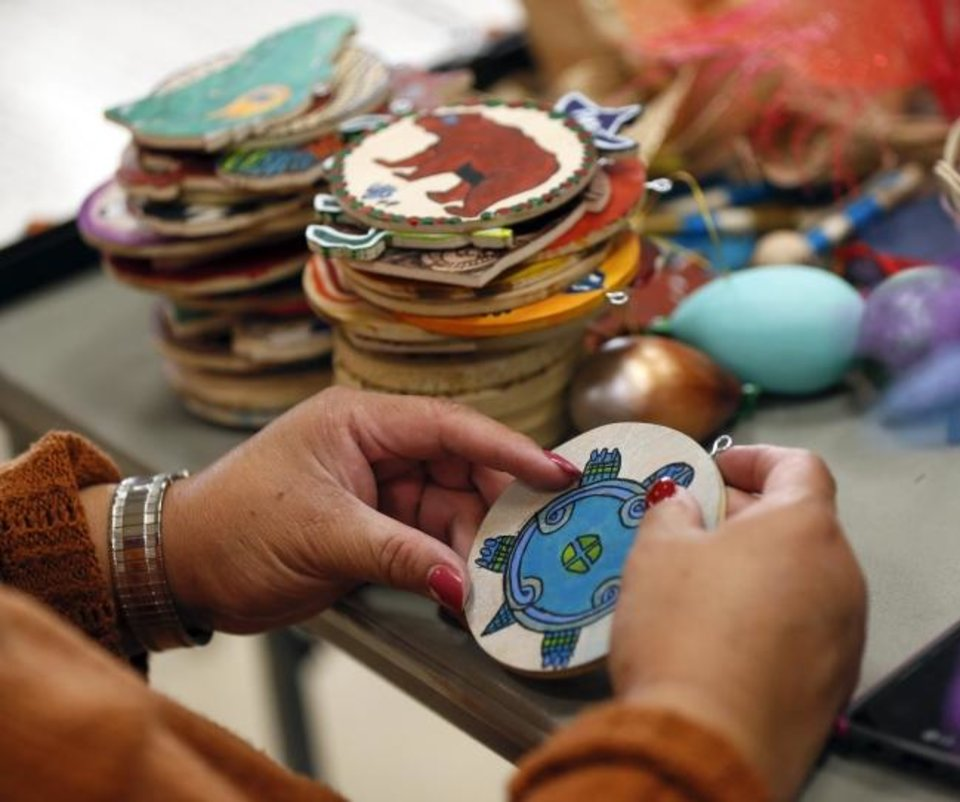 Photo -  Gwen Postoak sorts decorations Monday depicting the Chickasaw clan animals for the Chickasaw Nation Christmas tree for Red Earth Treefest at the OSU-OKC Student Center in Oklahoma City. [Nate Billings/The Oklahoman]