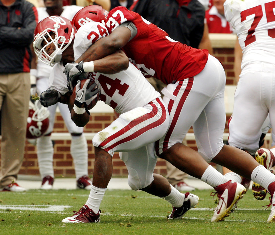 Photo - Chaz Nelson (37) brings down Brennan Clay (24) during the University of Oklahoma (OU) football team's annual Red and White Game at Gaylord Family/Oklahoma Memorial Stadium on Saturday, April 14, 2012, in Norman, Okla.  Photo by Steve Sisney, The Oklahoman