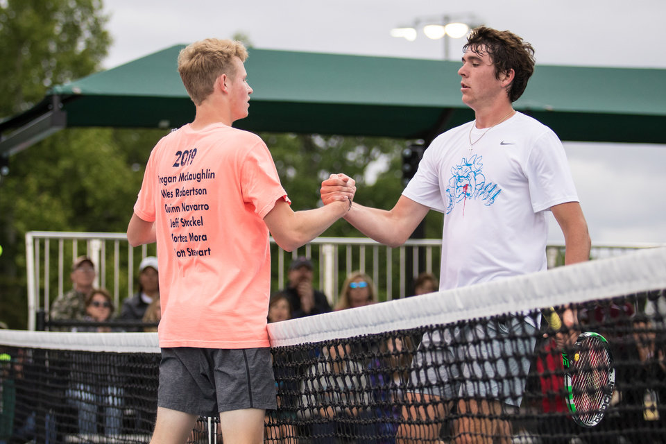Photo - Edmond North's Brogan McLaughlin shakes hands with Edmond Memorial's Chris Dyer during the 2019 OSSAA Men's Tennis Championships on May 11, 2019, in Oklahoma City at the OKC Tennis Center. (DEVIN LAWRENCE WILBER/for the Oklahoman)