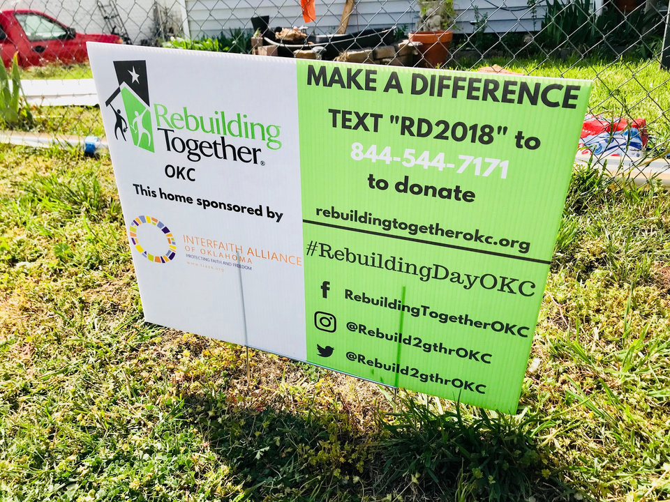 Photo -  A Rebuilding Together yard sign in front of a home in the Akers Park neighborhood of Oklahoma City lets passersby know that some of people working there are part of the Interfaith Alliance's Many Belief's Serving Together group. [Photo by Carla Hinton, The Oklahoman]