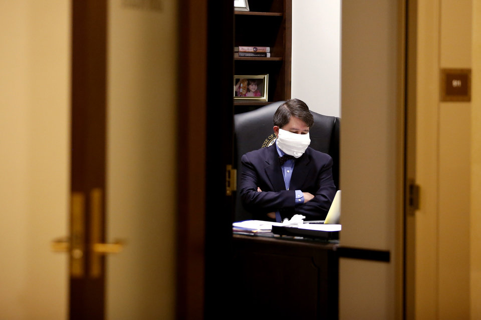 Photo - Rep. Andy Fugate watches a special session of the House of Representatives from his office at state Capitol in Oklahoma City, Monday, April 6, 2020. A skeleton crew of lawmakers was allowed in the House chamber as others watched from their offices during a special session of the House of Representatives. [Bryan Terry/The Oklahoman]