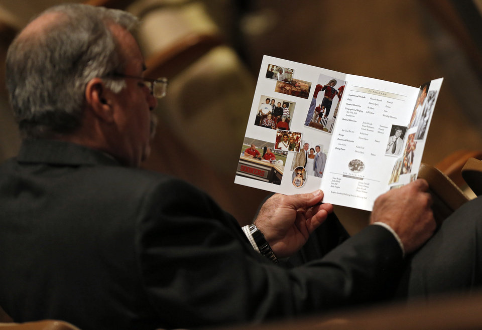 Photo - A mourner reads the funeral program during the funeral services for former University of Oklahoma football player Steve Davis at the First Baptist Church on Monday, March 25, 2013, in Tulsa, Okla. Davis died in a plane crash last week in Indiana. Photo by Chris Landsberger, The Oklahoman