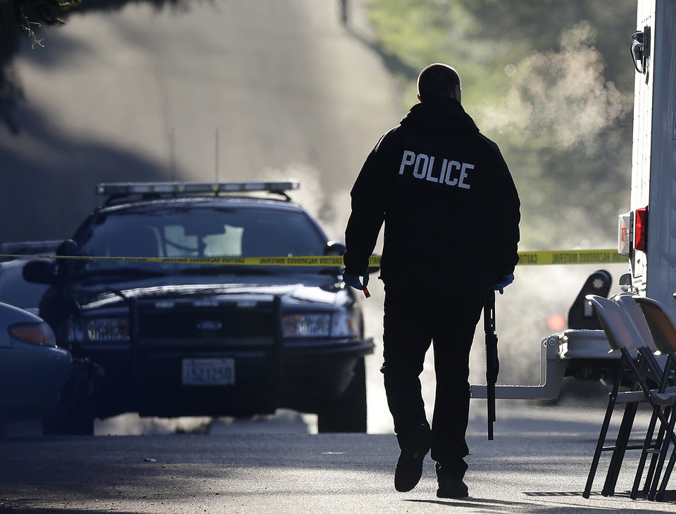 Photo - A police officer carries a shotgun and what appears to be a shell casing as officers collect evidence from the scene of an overnight shooting that left five people dead, including a suspect who was shot by arriving officers, police said early Monday, April 22, 2013, at an apartment complex in Federal Way, Wash. (AP Photo/Ted S. Warren)