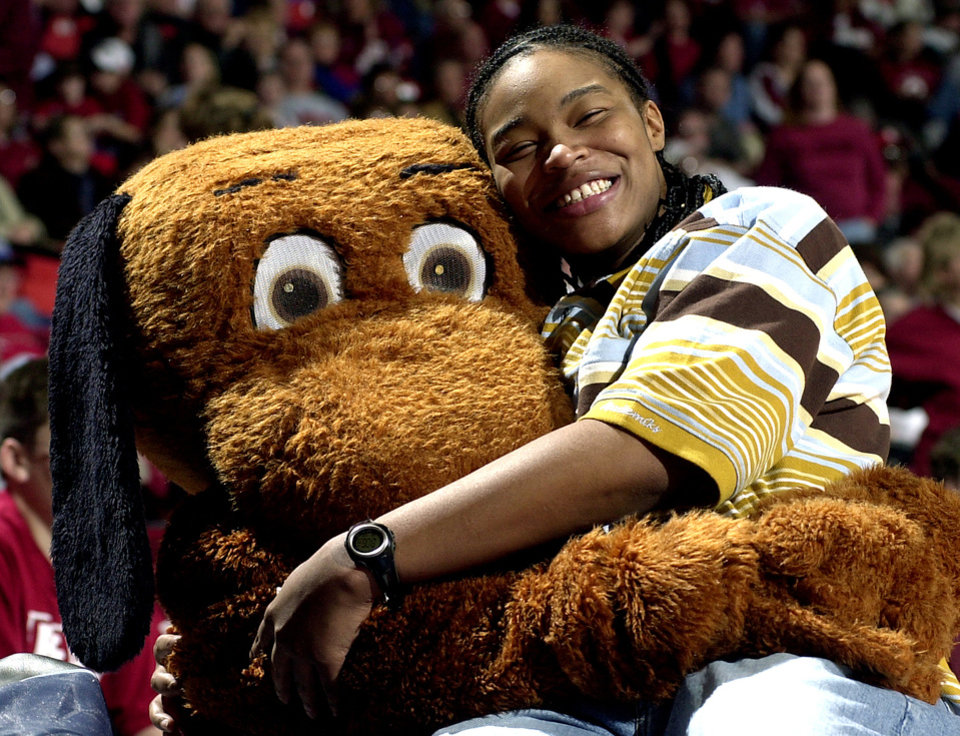 Photo - MASCOT: Former University of Oklahoma women's college basketball player Rosalind Ross gets a hug from Top Daug during the OU-Texas game this past week. Ross is now a WNBA player. Oklahoman staff Photo by Ty Russell.