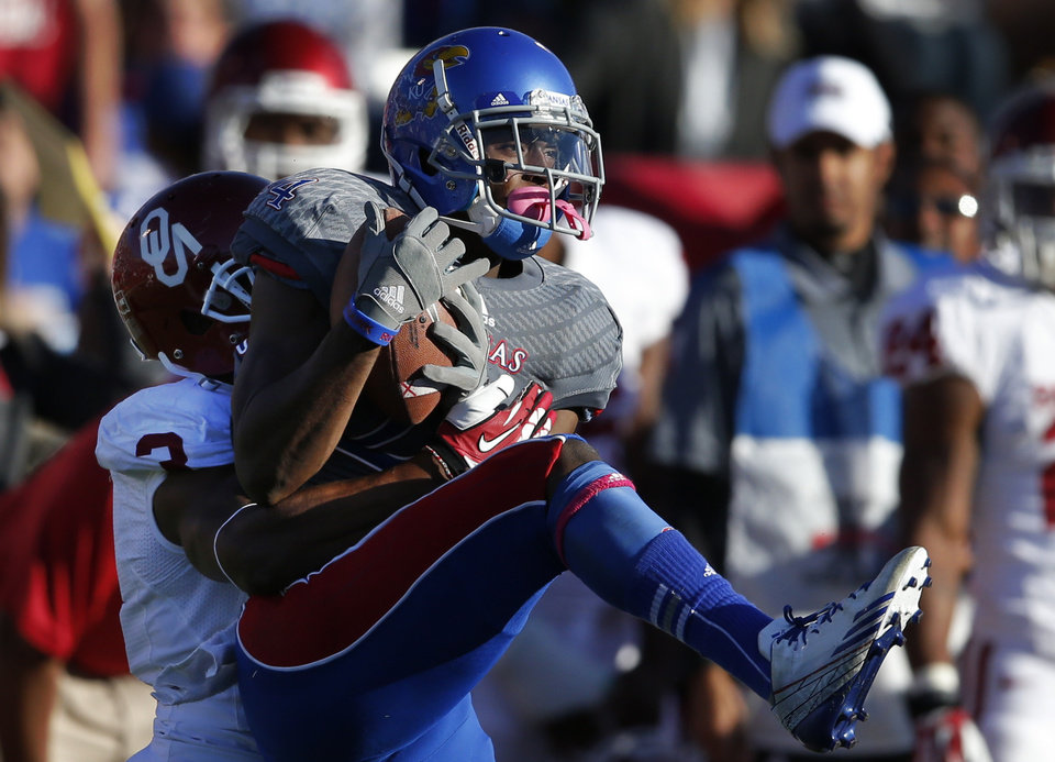 Photo -  Kansas cornerback JaCorey Shepherd, right, intercepts a pass intended for Oklahoma wide receiver Sterling Shepard (3) during the second half of an NCAA college football game in Lawrence, Kan., Saturday, Oct. 19, 2013. Oklahoma defeated Kansas 34-19. (AP Photo/Orlin Wagner)