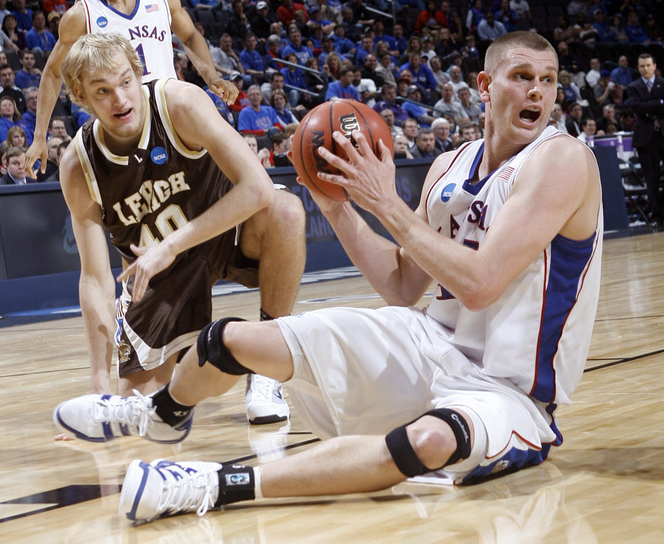 Photo - OKLAHOMA CITY REGIONAL / NCAA TOURNAMENT/ COLLEGE BASKETBALL: Kansas' Cole Aldrich (45) recovers a loose ball against Lehigh's David Safstrom (40) during the NCAA Men's first round basketball tournament game between the University of Kansas and Lehigh University at the Ford Center on Thursday, March 18, 2010, in Oklahoma City, Okla.  Photo by Chris Landsberger, The Oklahoman ORG XMIT: KOD