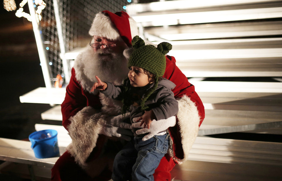Judah Hussain, 18 months, gets his photo taken with Santa during the opening ceremony of the Midwest City Holiday Lights Spectacular. Photos by Garett Fisbeck, The Oklahoman