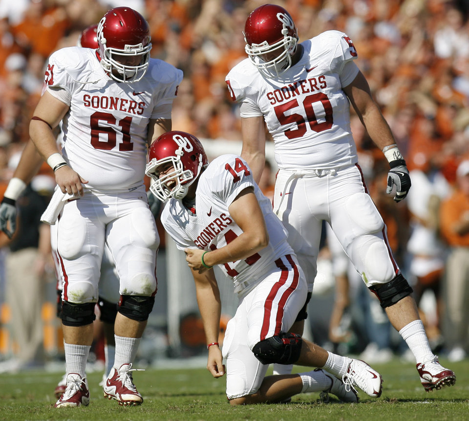Photo - OU's Sam Bradford reacts after an injury in front of teammates Ben Habern, left, and Brody Eldridge during the Red River Rivalry college football game between the University of Oklahoma Sooners (OU) and the University of Texas Longhorns (UT) at the Cotton Bowl in Dallas, Texas, Saturday, Oct. 17, 2009. Photo by Bryan Terry, The Oklahoman
