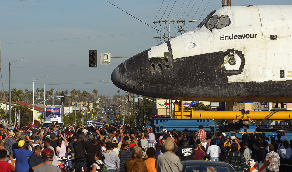 The space shuttle Endeavour is slowly moved down Crenshaw Blvd. at Slauson Ave., Saturday, Oct.13, 2012, in Los Angeles. The shuttle is on its last mission � a 12-mile creep through city streets. It will move past an eclectic mix of strip malls, mom-and-pop shops, tidy lawns and faded apartment buildings. Its final destination: California Science Center in South Los Angeles where it will be put on display. (AP Photo/Mark J. Terrill)