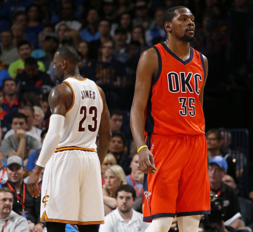 Photo - Oklahoma City's Kevin Durant (35) walks away in front of Cleveland's LeBron James (23) during an NBA basketball game between the Oklahoma City Thunder and the Cleveland Cavaliers at Chesapeake Energy Arena in Oklahoma City, Sunday, Feb. 21, 2016. Oklahoma City lost 115-92.  Photo by Bryan Terry, The Oklahoman