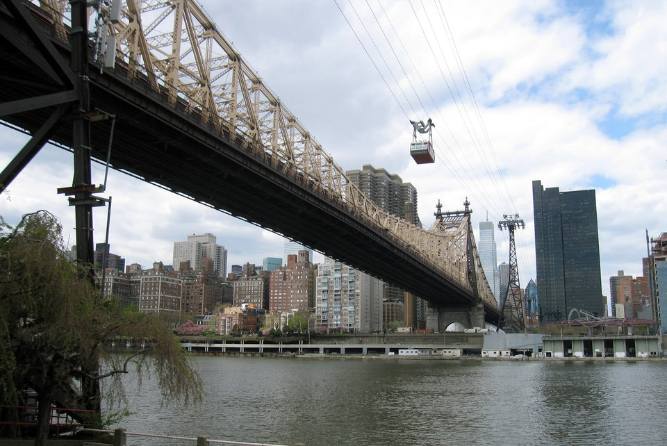 Photo - This May 1, 2014 photo shows the Roosevelt Island Tram above the Ed Koch Queensborough Bridge, crossing the East River to Roosevelt Island in New York City. The island is home to the Franklin D. Roosevelt Four Freedoms Park,  which offers scenic views of the city and was designed by renowned architect Louis I. Kahn.  (AP Photo/Beth J. Harpaz)