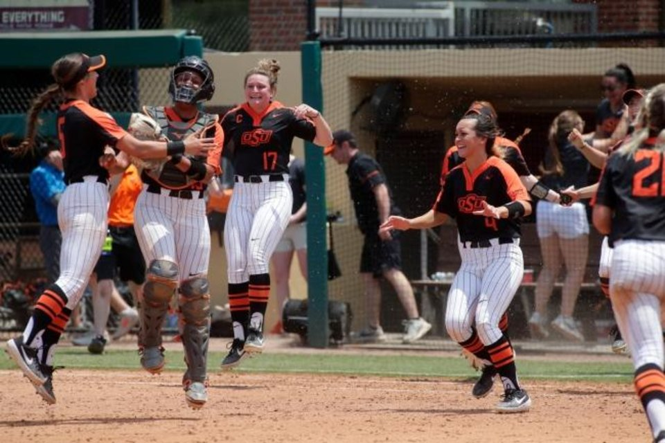 Photo -  Oklahoma State's Kiley Naomi (5), Rachel Dominguez (13), Elise LeBeouf (17) and Taylor Tuck (4) celebrate after the Cowgirls beat Florida State 3-2 Saturday to win their NCAA super regional in Tallahassee, Fla. [Alicia Devine/Tallahassee Democrat]
