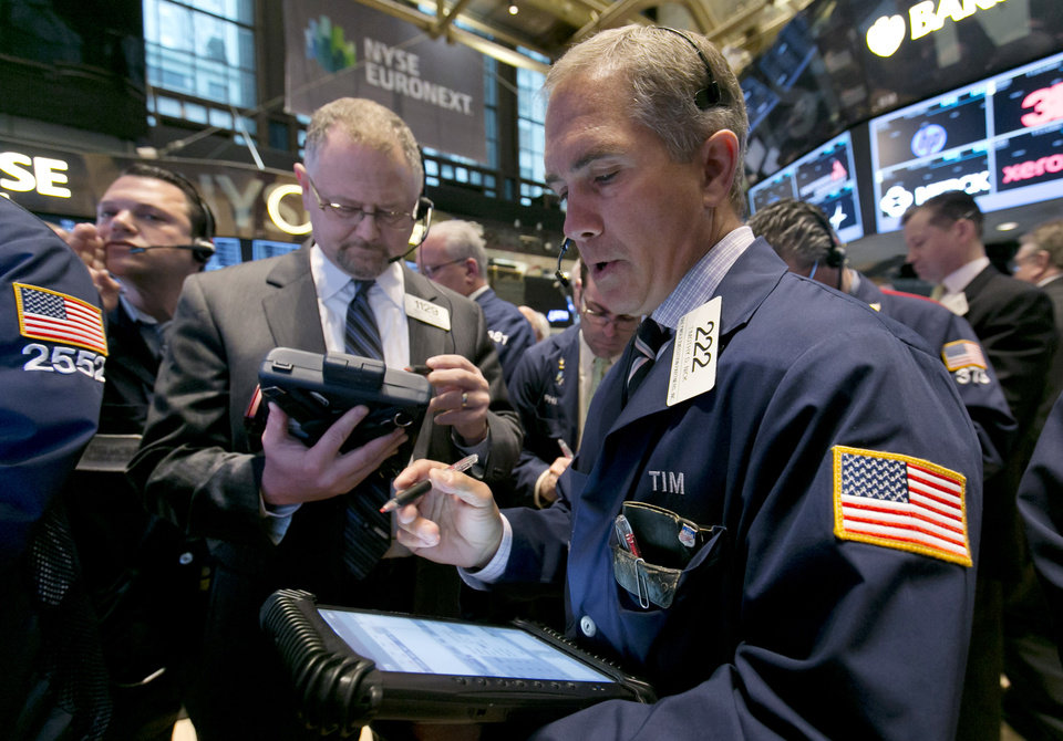 Photo - Trader Timothy Nick, right, works on the floor of the New York Stock Exchange, Tuesday, April 8, 2014. Stocks were mixed in early trading on Tuesday after a three-day slump. Investors will start to focus on company earnings this week. (AP Photo/Richard Drew)