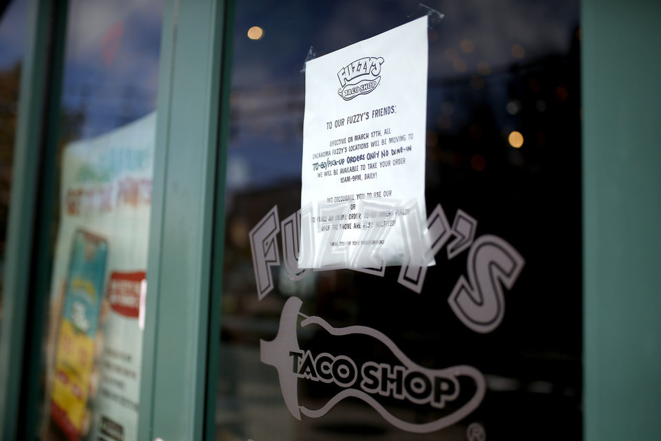 Photo - A note on the door of Fuzzy's Taco Shop is pictured in Bricktown in Oklahoma City, Wednesday, March 18, 2020. [Sarah Phipps/The Oklahoman]