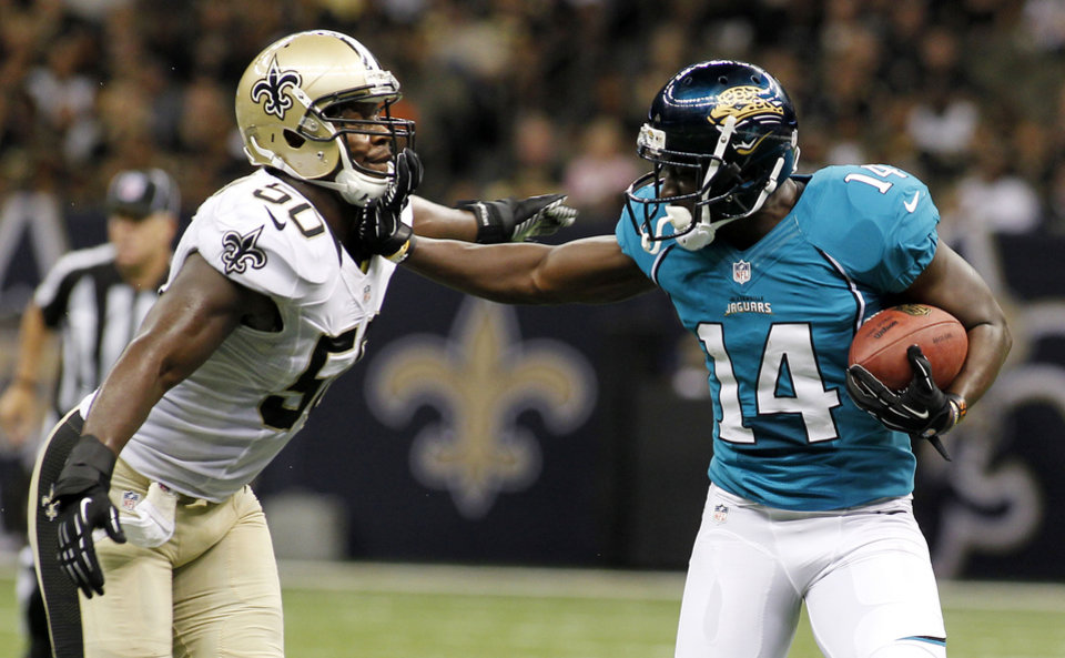 Jacksonville Jaguars wide receiver Justin Blackmon (14) rushes against New Orleans Saints linebacker Curtis Lofton (50) in the first half of a preseason NFL football game in New Orleans, Friday, Aug. 17, 2012. (AP Photo/Jonathan Bachman)