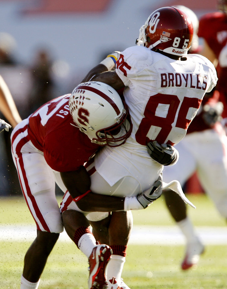 Photo - Oklahoma's Ryan Broyles (85) is hit by Stanford's Johnson Bademosi (27) that forced a fumble on a punt reception by Broyles during the second half of the Brut Sun Bowl college football game between the University of Oklahoma Sooners (OU) and the Stanford University Cardinal on Thursday, Dec. 31, 2009, in El Paso, Tex.   Photo by Chris Landsberger, The Oklahoman