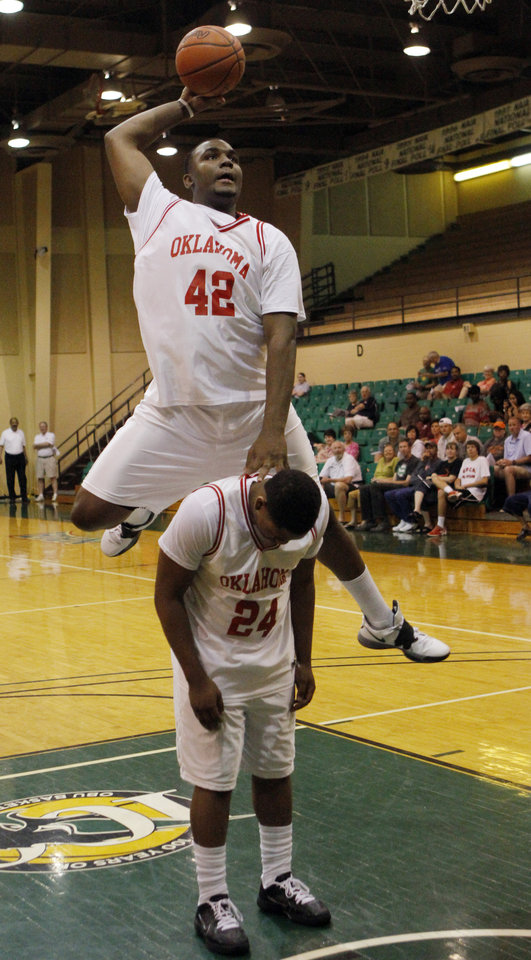 Photo - Oklahoma forward Shaquille Morris jumps over team mate Cornell Neal in a dunk contest before the Faith 7 Bowl All Star game in Shawnee where the Oklahoma team won 101 - 95. Photo by KT KING, The Oklahoman