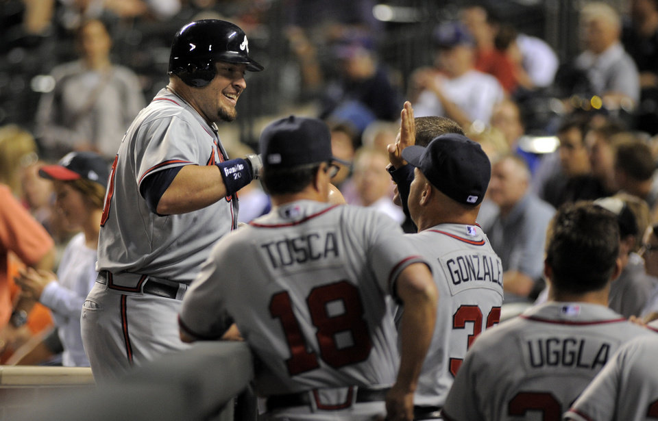 Photo -   Atlanta Braves' Eric Hinske celebrates a two run home run off Colorado Rockies relief pitcher Edgmer Escalona with teammates during the 11th inning of a baseball game Friday, May 4, 2012, in Denver. (AP Photo/Jack Dempsey)