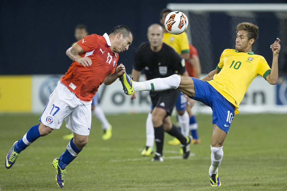 Photo - Brazil's Neymar, right, battles for the ball with Chile's Gary Medel during the second half of their international friendly soccer match, Tuesday, Nov. 19, 2013 in Toronto. (AP Photo/The Canadian Press, Chris Young)