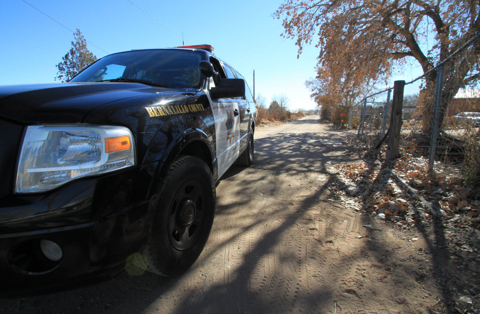 Photo - A Bernalillo County sheriff's deputy blocks the dirt road that leads to a home where detectives on Sunday, Jan. 20, 2013, were investigating the deaths of five people who were shot to death south of Albuquerque, N.M. Authorities say a teenager has been arrested and booked on murder and other charges in connection with the shootings. (AP Photo/Susan Montoya Bryan)