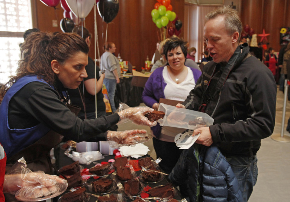 Duran Sloan with Sam's Club Norman puts chocolate cake into a container for Jim LaDue of Norman during the annual Chocolate Festival benefiting the Firehouse Art Center on Saturday, February 5, 2011, in Norman, Okla.  Photo by Steve Sisney, The Oklahoman