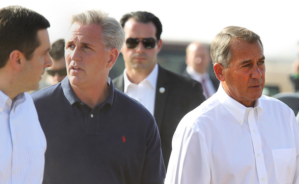 Photo - Republican Reps. Devin Nunes, left,and Rep. Kevin McCarthy, center, and House Speaker John Boehner, right, prepare for a news conference about the drought situation in the Central Valley, Wednesday, Jan. 22, 2014, near Bakersfield, Calif. Boehner visited a dusty California field, joining Central Valley Republicans to announce an emergency drought-relief bill to help farmers through what is certain to be a devastating year. If passed, the bill that's already stirring controversy would temporarily halt restoration of the San Joaquin River designed to bring back the historic salmon flow, among other measures. Farmers want that water diverted to their crops. (AP photo/The Bakersfield Californian, Casey Christie) MAGS OUT  ONLINES OUT  TV OUT  NO SALES