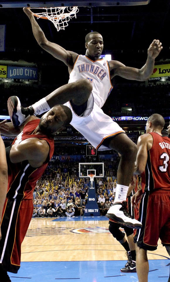 Oklahoma City's Kendrick Perkins (5) dunks over Miami's Dwyane Wade (3) after a dunk during the NBA basketball game between the Miami Heat and the Oklahoma City Thunder at Chesapeake Energy Arena in Oklahoma City, Sunday, March 25, 2012. Photo by Sarah Phipps The Oklahoman