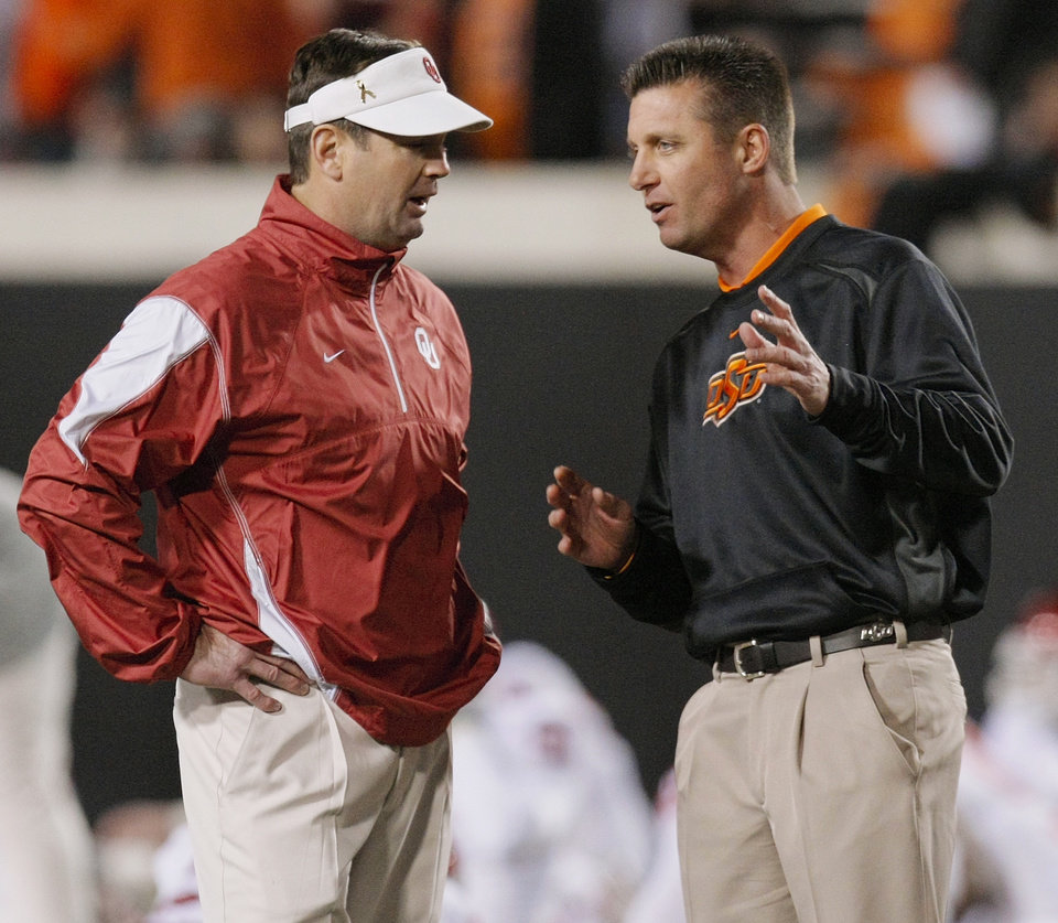 Photo - OU head coach Bob Stoops, left, and OSU head coach Mike Gundy talk before the Bedlam college football game between the University of Oklahoma Sooners (OU) and the Oklahoma State University Cowboys (OSU) at Boone Pickens Stadium in Stillwater, Okla., Saturday, Nov. 27, 2010. Photo by Nate Billings, The Oklahoman