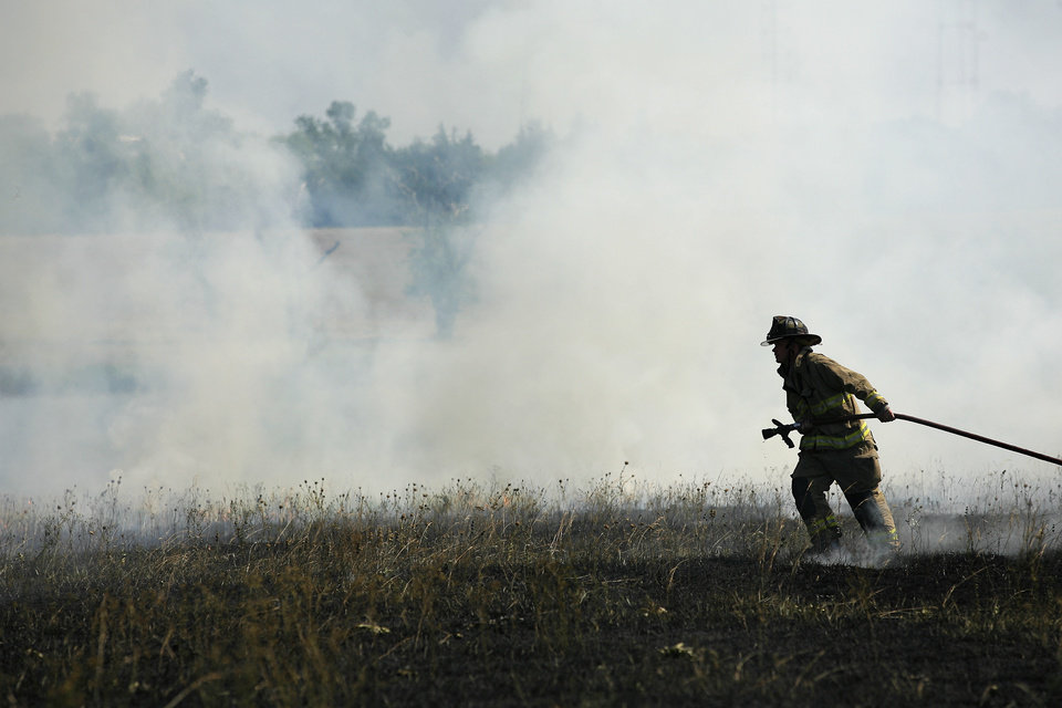 A firefighter battles a grass fire that burned on the OPUBCO campus, Saturday, July 2, 2011.  Photo by Garett Fisbeck, The Oklahoman