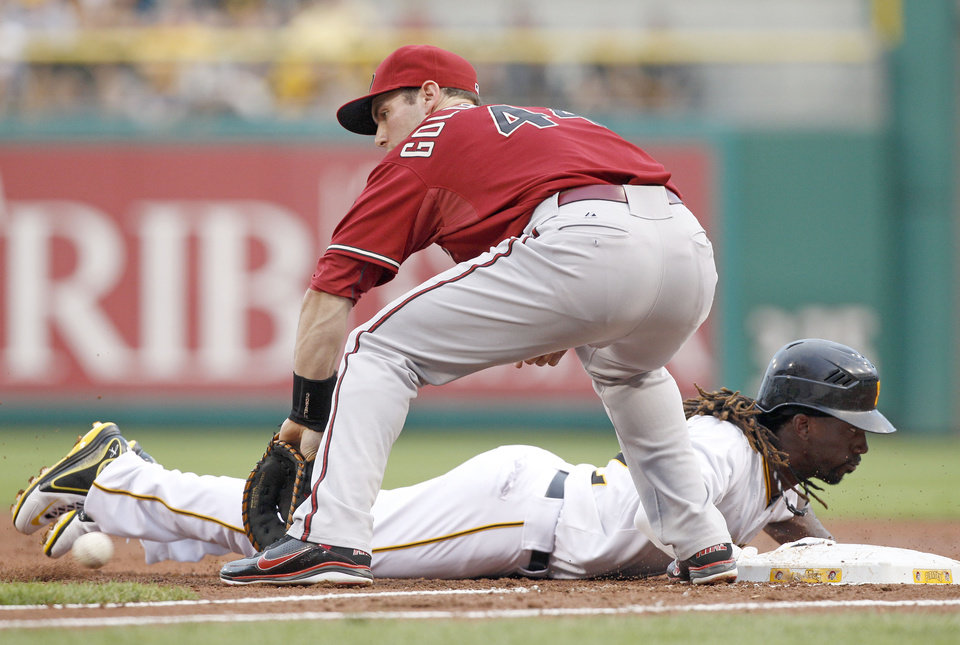 Photo -   Pittsburgh Pirates' Andrew McCutchen, bottom, dives back to first as Arizona Diamondbacks first baseman Paul Goldschmidt reaches for the pick-off attempt by Diamondbacks starting pitcher Ian Kennedy in the first inning of a baseball game Wednesday, Aug. 8, 2012, in Pittsburgh. (AP Photo/Keith Srakocic)